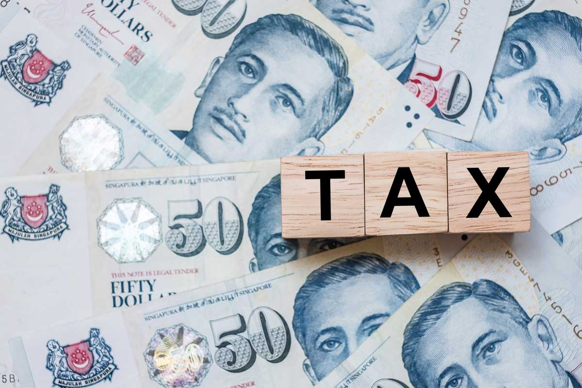 singapore currency with wooden blocks spelling out tax as concept for double tax deduction iras