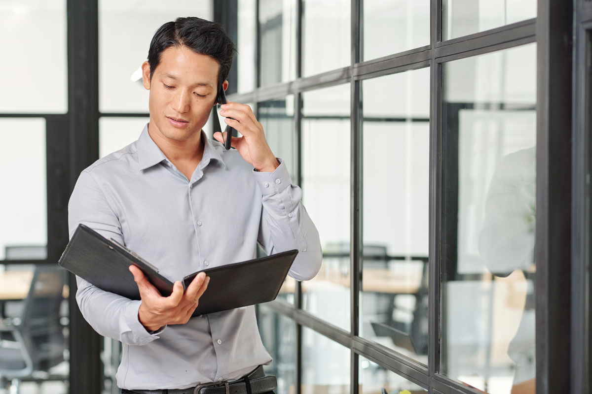 male auditor speaking on a mobile phone while reading corporate financial documents