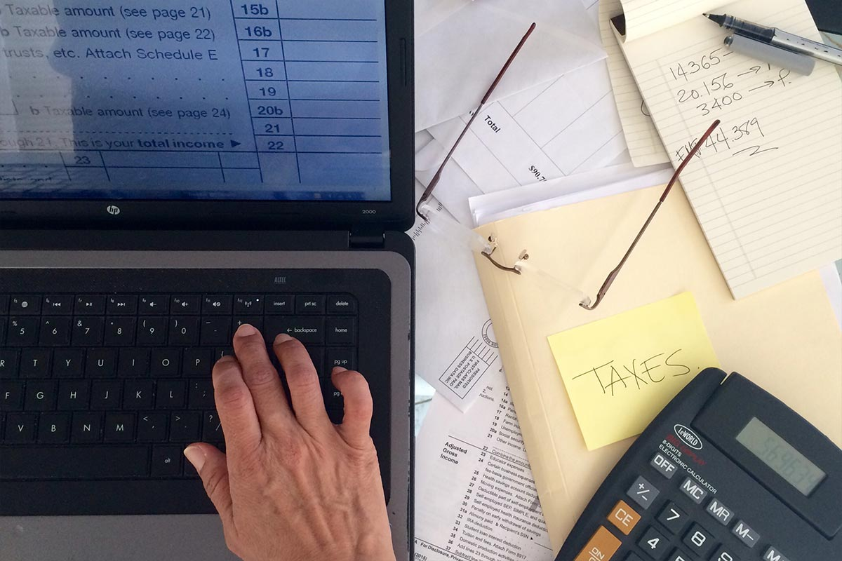 Man using laptop to compute personal income tax relief figures on a desk full of documents, a folder labelled taxes, eyeglasses and a black calculator