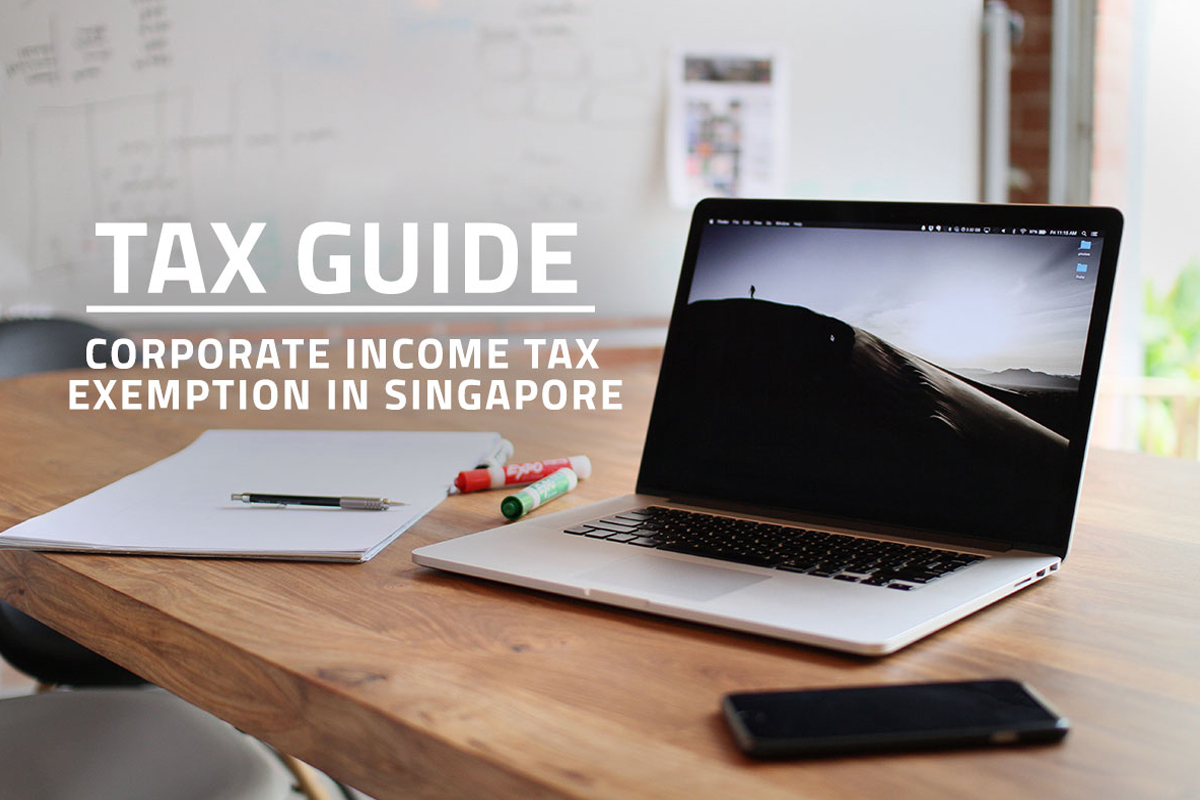 words tax guide corporate income tax exemption in Singapore overlaying background of notepad, laptop and mobile phone on a table in startup company meeting room